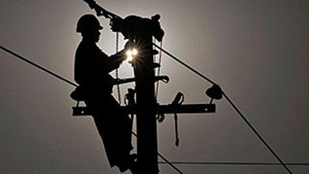 Technicien en train de réparer une panne sur un poteau électrique