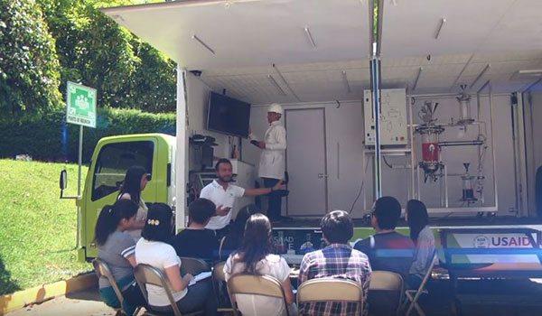 """Des élèves assistant à l'explication de la fabrication du biodiésel dans le """"Steam Truck"""""""